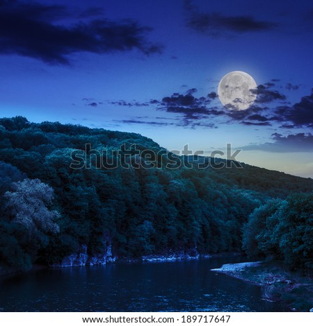 calm river flowing between green mountains on a dark summer night in moon light