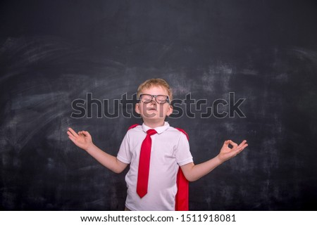 Calm school boy meditating against blackboard in class. Child in yoga pose. Confidant and health breathing. Relaxed kid in uniform. Back to school.