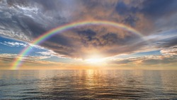 Calm sea before storm with amazing rainbow at sunset