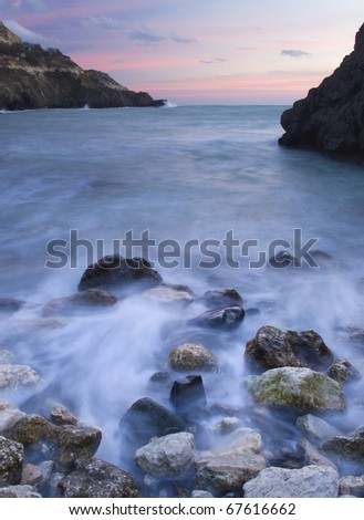 Calm sea during sundown. Stone and mist on water