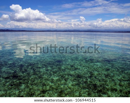 Calm sea in shallow water with cloud reflected on water surface, Caribbean, Panama - stock photo