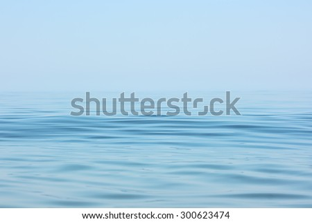 Calm sea surface. Seascape in early morning hours under clear skies.