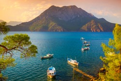 Calm sea with boats and big mountain. Sunset in the mediterranean. Adrasan, Antalya, Turkey.
