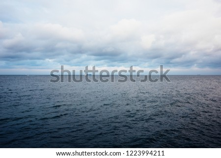 Calm sea with little boats in the distance on horizon. Ocean water surface with rippled waves.