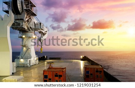 calm seas as seen from a modern offshore vessel with containers loaded on deck and large crane swung out to its aft #1219031254