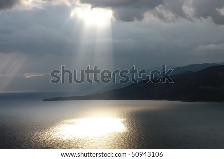 Calm seascape with stormy sky where sun-rays get through the clouds.