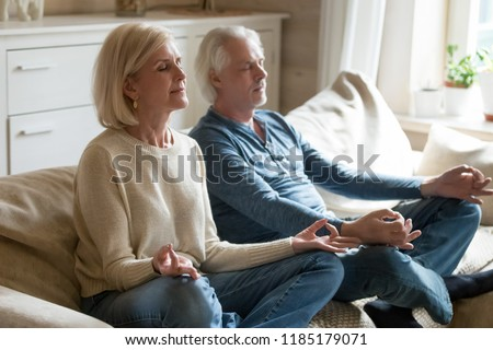 Calm senior middle aged couple practicing yoga together sitting in lotus pose on sofa, mindful peaceful mature man and woman meditating relaxing in living room at home, old people healthy lifestyle