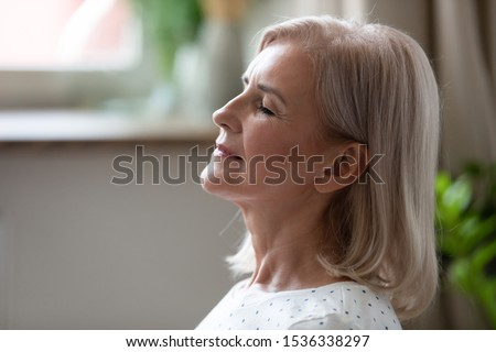 Calm serene middle aged woman meditating with eyes closed inhaling fresh air relaxing indoors, happy healthy old mature lady enjoying resting feel peace of mind doing breathing yoga exercises at home