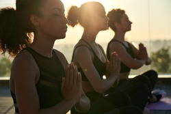 Calm serene sporty young african american ethnic woman meditate sit namaste eyes closed doing breathing exercises practice relaxing at outdoor group multiethnic yoga class in morning sunrise light.