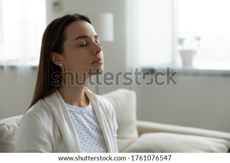 Calm serene woman resting sitting on couch in modern living room closed her eyes breath fresh humidified air. Fatigue relief repose, boost inner balance and mindfulness, meditation practice concept Photo stock ©