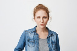 Calm serious caucasian ginger girl with hair combed in bun, expressing irritation or indifference while standing over gray background. Sister do not like shopping with friend cause it is boring