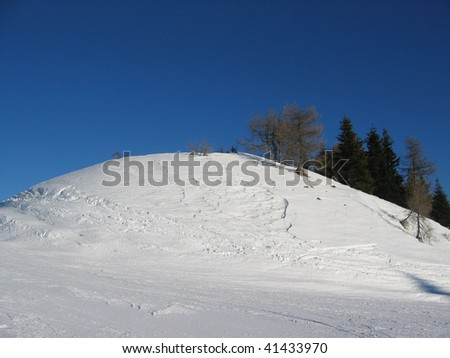 Calm snow-covered hill with empty blue sky