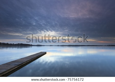 Calm sunset with a jetty on a lake