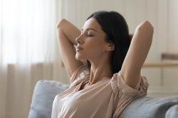 Calm tired young woman attractive face lounge leaning on sofa napping with eyes closed at home, serene lady hold hands behind head relaxing breathing fresh air sit on comfortable couch in living room