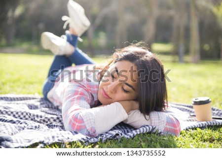 Calm tranquil girl relaxing in park. Young woman lying on plaid outdoors with closed eyes. Tranquility and nature concept #1343735552
