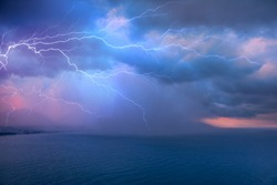 Calm tropical blue sea under amazing storm clouds with lightning
