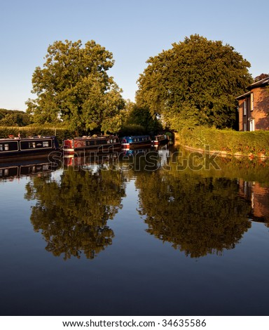 Calm view of the canal near Ellesmere with the barges reflected in the water