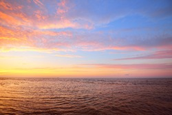 Calm water of the Baltic sea under the colorful pink sunset clouds. A view from the sandy shore. Riga bay, Latvia. Epic seascape. Idyllic autumn scene. Meteorology, ecology, environmental conservation