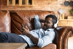 Calm young african ethnicity man in glasses wearing headphones, relaxing on comfortable couch listening favorite music, choosing tracks in online mobile application, casual hobby weekend lazy pastime.