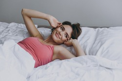 Calm young fun satisfied positive caucasian woman 20s wearing pajamas lying on bed wrap covered under blanket duvet on pillow stretching rest relax at home. Good mood night morning bedtime concept.