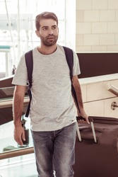 Calm young man walking with luggage. Handsome Hispanic traveler strolling at airport. Travel concept