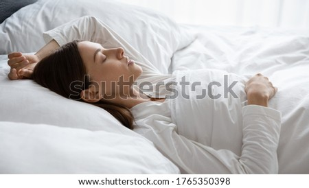 Calm young woman sleep peacefully in comfortable white bed on fluffy pillow see dreams in morning, peaceful millennial female relax rest take nap in bright hotel or home bedroom, relaxation concept ストックフォト ©