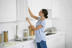 Calm young woman standing in the kitchen and taking food from the cupboard
