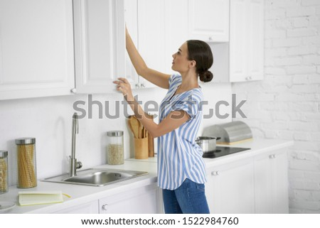Calm young woman standing in the kitchen and taking food from the cupboard Stock photo ©