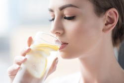 Calm youthful lady refreshing herself with lemon water