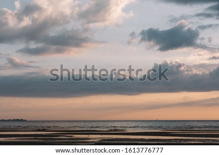 Calming scenic landscape above the sea. Gentle tones of the scenery. Orange and blue tones of sky. Beauty world. Travel and vacation. Natural background concept. Inspirational photo.