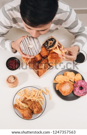 Calorie burger with french fries, people eating at cafe table, unhealthy lunch #1247357563