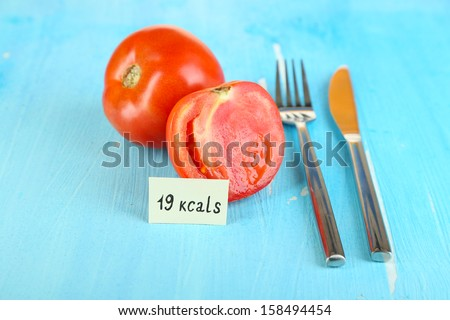 Calorie content of tomato on wooden table close-up