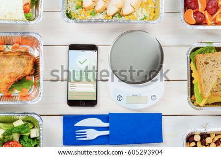 Calorie counter app, a bottle of water, a kitchen scale on the wooden surface. Lean fish, lettuce salad, cheese sandwiches and plastic cutlery, fruits and nuts. Healthy weight loss.