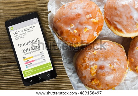 Calorie counter concept - mobile phone with calorie counter app on the screen and doughnuts. Wooden table as background