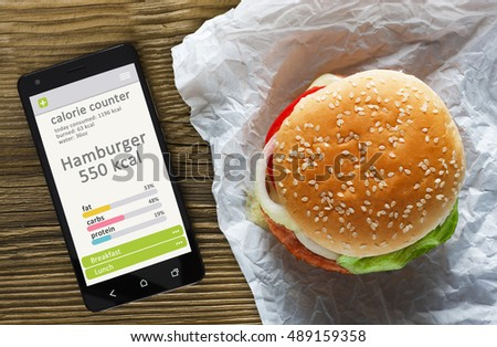 Calorie counter concept - mobile phone with calorie counter app on the screen and hamburger. Wooden table as background