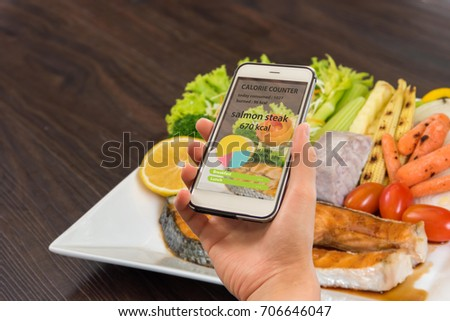 Calorie counter concept - mobile phone with calorie counter app on the screen and Salmon fillets. Grilled salmon, salmon steak on old wooden table, vintage style