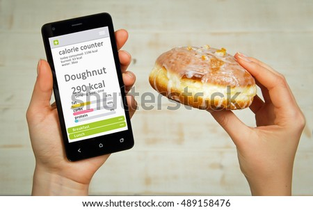 Calorie counter concept - young woman holding mobile phone with calorie counter app on the screen.