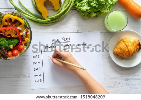 Calories control, meal plan, food diet and weight loss concept. top view of hand filling meal plan on weekly table with salad and fresh vegetable on dining table