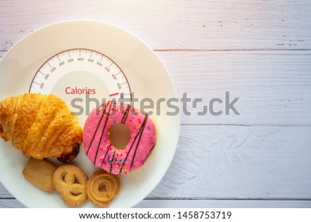 Calories counting and food control concept. doughnut ,croissant and cookies on white plate with tongue scales for Calories measuring