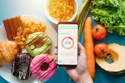 Calories counting and food control concept. woman using Calorie counter application on her smartphone with fresh vegetables, dessert and donuts on dining table