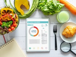 Calories counting, diet , food control and weight loss concept. tablet with Calorie counter application on screen at dining table with salad, fruit juice, bread and vegetable
