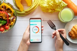 Calories counting , diet , food control and weight loss concept. woman using Calorie counter application on her smartphone at dining table with salad, fruit juice, bread and vegetable