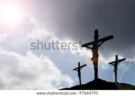 calvary crucifixion with dark sky and rays of light - stock photo
