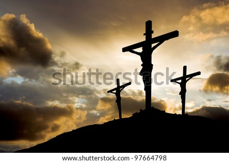 calvary crucifixion with sun setting behind - stock photo