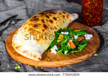 Calzone pizza, filled herbs, cheese and tomatoes