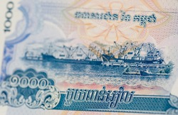 Cambodian banknote for 1000 Riel showing ships at the  Port of Sihanoukville (Kampong Saom) on the Indian Ocean coast of the nation.   Used banknote, viewed at angle with selective focus.