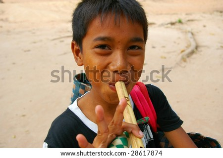 Cambodian boy playing one of the flutes he is trying to sell, Bayon Temple, Siem Reap, Cambodia.