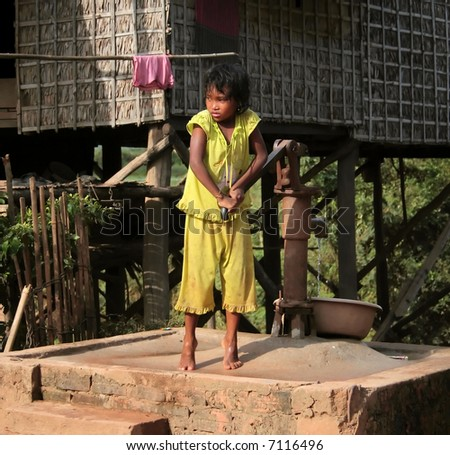 Cambodian girl pumping water into a basin