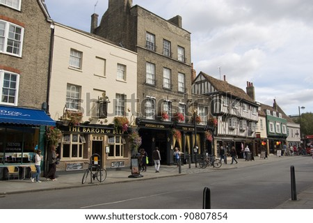 CAMBRIDGE, ENGLAND - SEPTEMBER 19: Shoppers walking by historic pubs of Bridge Street on September 19 2011.  The street is famous for its drinking establishments and has been for hundreds of years.