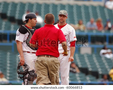 CAMDEN, NJ - AUGUST 15: Camden Riversharks relief pitcher Tim Bittner (facing right) stands after injuring his arm while the trainer runs out in a game August 15, 2010 in Camden, NJ.